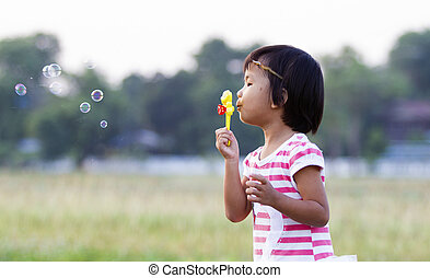 Asian little girl is blowing a soap bubbles