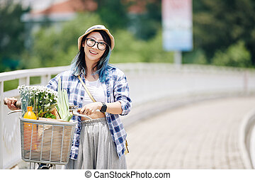 Asian woman walking with bicycle