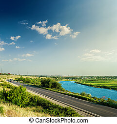 asphalt road and river under sunset in blue sky with clouds