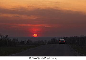Asphalt road at red sunset