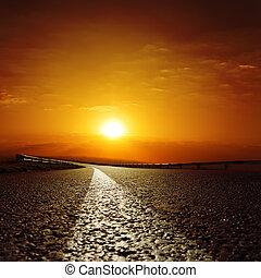 asphalt road to red sunset