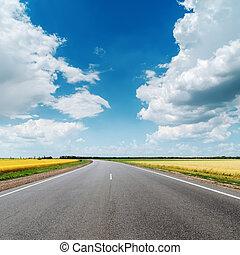 asphalt road under clouds in blue sky