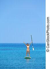 Aspirational beach lifestyle woman on paddleboard