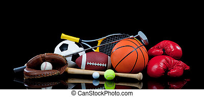 A group of sports equipment on black background including tennis, basketball, baseball, american fotball and soccer and boxing equipment on a black background with copy space