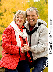 Photo of aged couple enjoying themselves in autumn forest