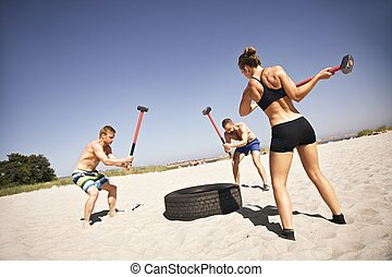 Three strong athletes doing hammer strike on a truck tire during crossfit exercise outside on beach. Muscular active people in 20s training to maintain healthy lifestyle