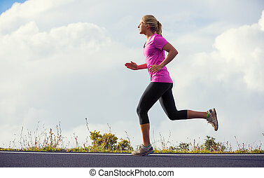 Athletic woman jogging outside, training outdoors. Running on road at sunset