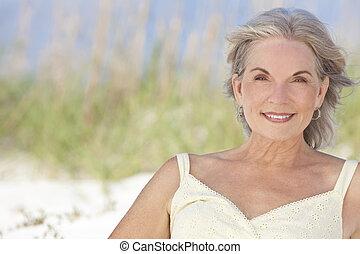 Attractive Elegant Senior Woman Sitting At A Beach