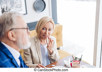 attractive elegant woman showing her husband to show his mouth after eating cake