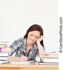 Attractive happy red-haired girl studying for an examination