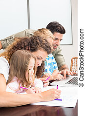 Attractive parents colouring and using laptop with their children at home in kitchen