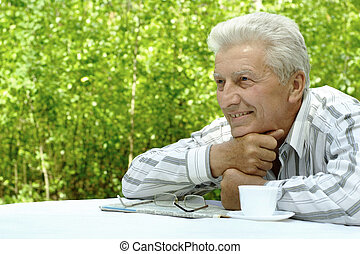 older man reading newspaper