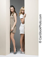 Attractive girls hiding theirselves behind the wall