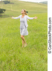 young girl with arms outstretched on grassland