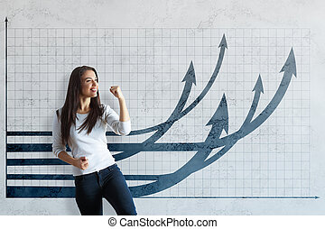 Attractive young woman celebrating success on concrete background with grid and upward chart arrows. Financial growth concept