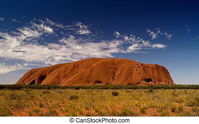 Uluru in red, blue cloudy sky, bush in front, full