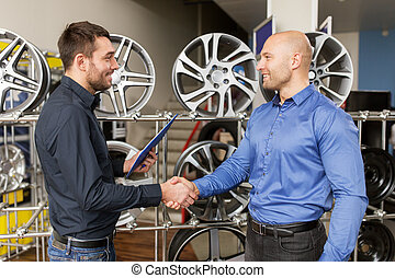 auto business owner and wheel rims at car service