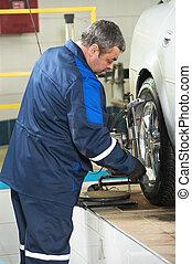 auto mechanic at wheel alignment work