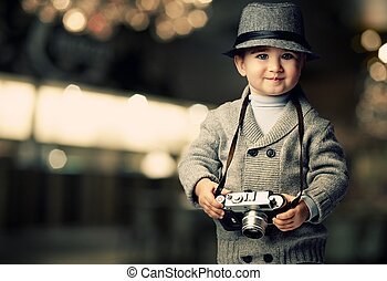 Baby boy with retro camera over blurred background.