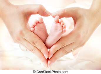 baby feet in mother hands - hearth