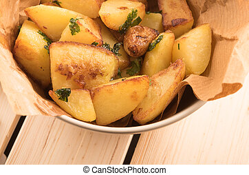 baked potato with garlic in a pan close-up, on a wooden background