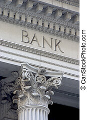 "Neoclassical architechture sports a column with the word ""BANK"" above it. Neoclassical architechture sports a column with the word ""BANK"" above it."
