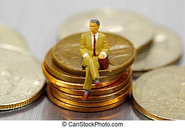 Miniature Businessman Sitting on Pennies