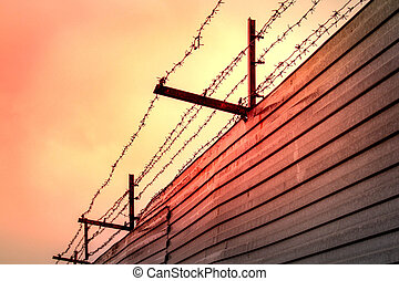 Barbed wire stretched over rusty brackets mounted on a fence made of metal sheets against the backdrop of the red sunset sky