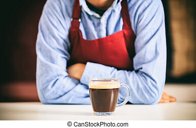 Barista in front of a cup of coffee