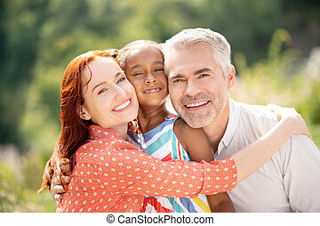 Beaming wife hugging her husband and daughter