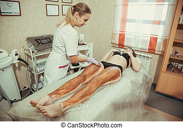 Beautician and woman in spa salon. Chocolate massage.