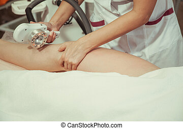 Beautician makes the vacuum massage cellulite young woman. Cosmetic procedure.