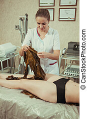 Beautician puts algae on a young woman in a spa salon.