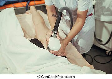 Beautician removes cellulite young woman in a beauty salon.