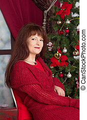 adult woman in a red sweater against Christmas tree