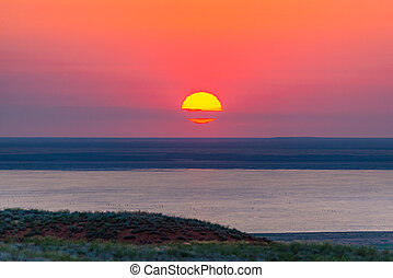 Beautiful bright red sunset over the lake and steppe