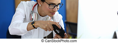 Beautiful businesswoman in white shirt and glasses play computer game with joystick.