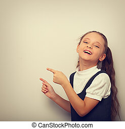 Beautiful excited laughing fun kid girl pointing the two fingers on empty space. Vintage toned portrait