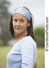 Portrait beautiful looking senior woman with headband posing outdoor in park, friendly, happy and relaxed smiling, with copy space and blurred background.