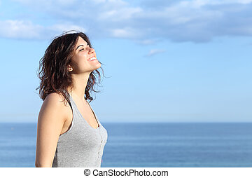 Beautiful girl breathing and smiling on the beach with the sea and blue sky in the background