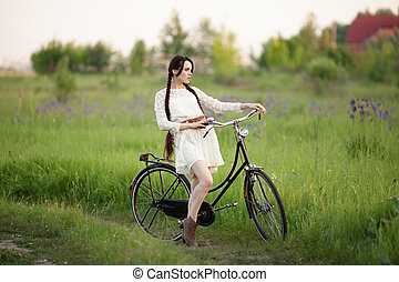 Beautiful girl in vintage white dress with old bicycle on the green summer field.