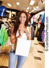 Beautiful happy brunette girl with shopping bag in a sport outlet
