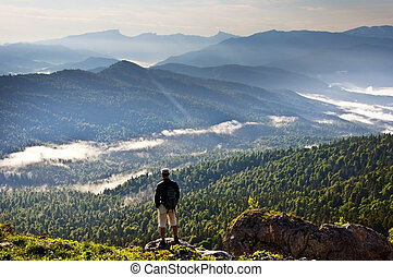 Beautiful mountains landscape - Caucasian mountains and person. Man standing on peak of mountains and looking to far away