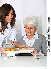 Beautiful nurse bringing meal tray to old woman at nursing home