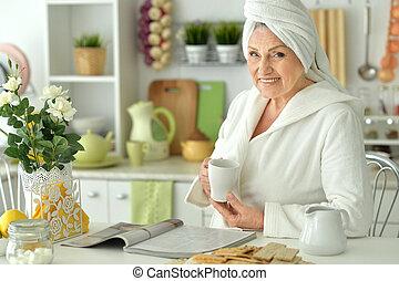 Beautiful older woman reading magazine