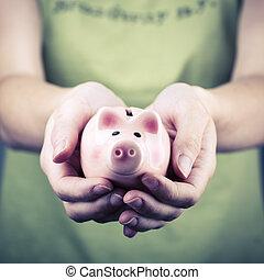 beautiful pig money box in woman hand