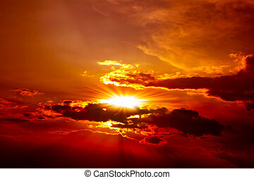 Beautiful red sunset above the clouds with rays of light
