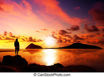 Silhouette of man reflecting while looking at a gorgeous sunset