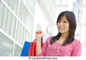 Beautiful young Asian girl holding paper bags, modern building as background