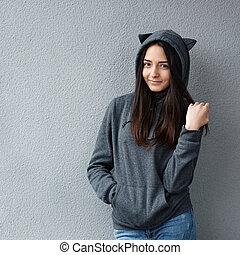 beautiful teenage girl standing against wall